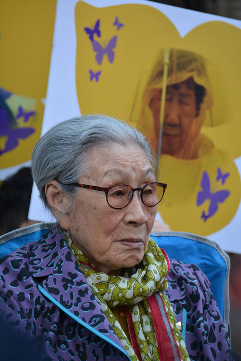 Comfort Women: Former comfort woman Kim Bok Dong at the weekly demonstration in front of the Japanese embassy in Seoul, South Korea.  A poster of a butterfly (sympol of the Comfort Women) with an image of Kang Il Chul who passed away in 2017.