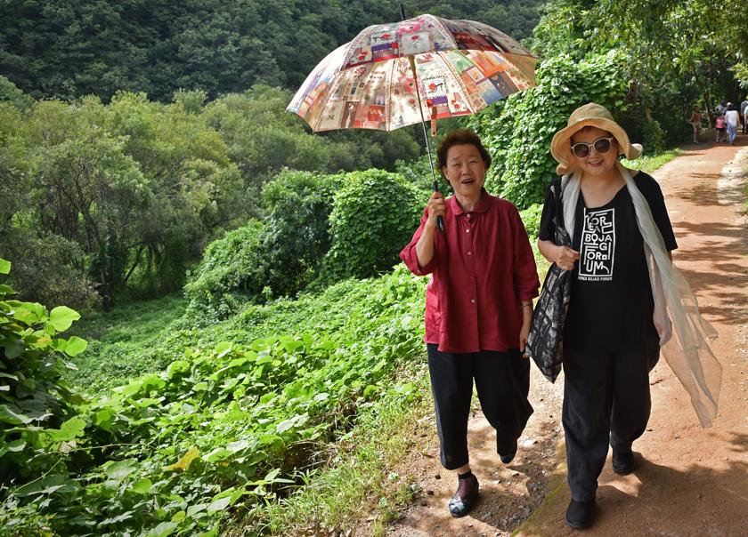 Bojagi artists Insook Choi and Chunghie Lee walking to see the petroglyphs in Bangudae near Ulsan, South Korea.