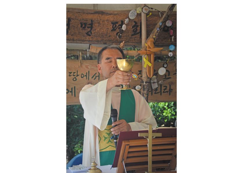 Father Sunghwan Kim celebrates Mass in a makeshift outdoor chapel near the naval base in Gangjeong, Jeju island, South Korea
