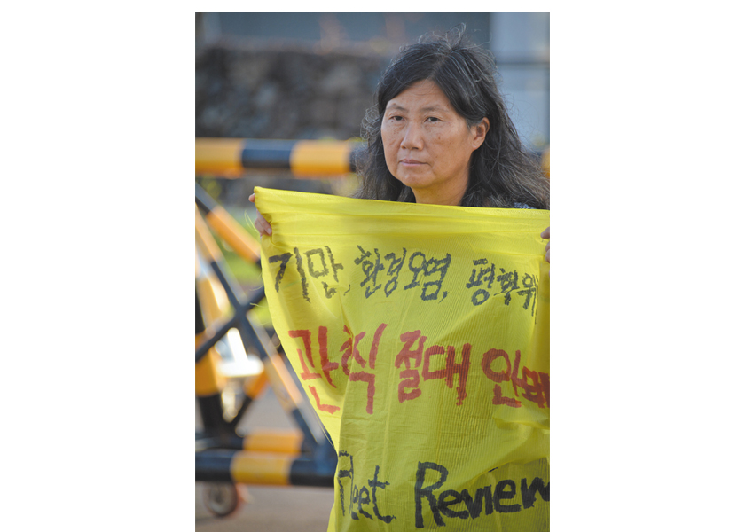 Sunhee Choi holds a sign protesting the planned International Fleet Review, a parade of naval firepower planned for October 2018.  Naval base in Gangjeong, Jeju island, South Korea