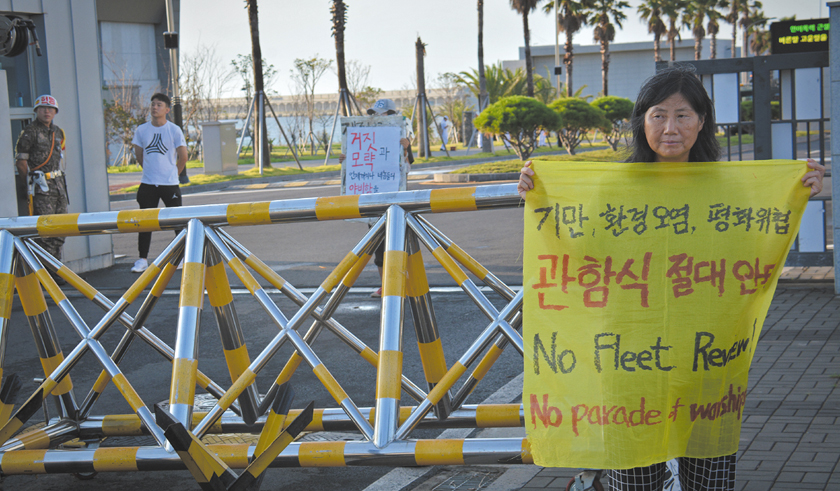 Sunhee Choi protests in front of the main gate to the naval base at Gangjeong, Jeju island, South Korea