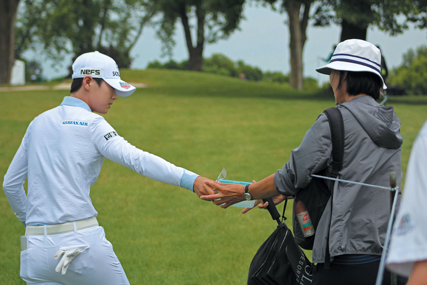 Sung Hyun Park's mother, Keum Ja lee, passes food in a Tupperware container as she walks down the ninth fairway at Hazeltine.