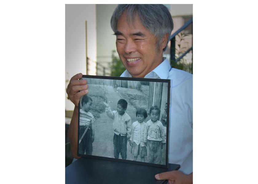 Adopted Korean Mosiac Hapa tour: Shinchon historian Myong-sik Kim with photo of hapa kids in Shinchon in the 1960s