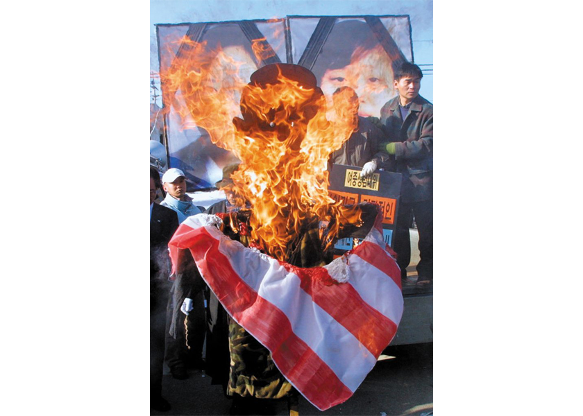 Protesters burn an effigy of U.S. President George W. Bush in response to the 2002 incident in which an American military vehicle crushed two 14-year-old girls to death.