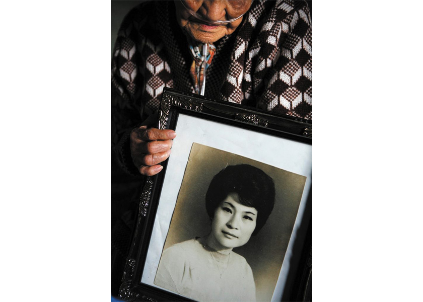 A former camp town prostitute named Bae, holds a photo of herself in her 20s.  Camp Casey in Dongducheon, South Korea.